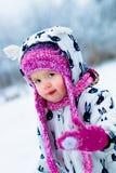 Barn i snöig dag Behandla som ett barn flickan i vit snowsuite, och rosa färghatten, kängahandskar i snövintern parkerar Royaltyfri Bild
