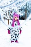 Barn i snöig dag Behandla som ett barn flickan i vit snowsuite, och rosa färghatten, kängahandskar i snövintern parkerar Arkivfoton