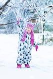 Barn i snöig dag Snönedgångar från trädet Behandla som ett barn flickan i vit snowsuite, och rosa färghatten, kängahandskar i vin Royaltyfri Bild