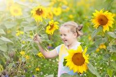 Barn i solrosfält Ungar med solrosor royaltyfri bild