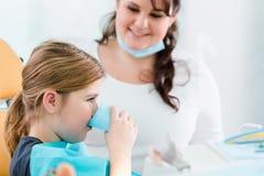 Barn i tandläkarekirurgi som spolar tänder med vatten Arkivfoto