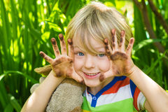 Barn i trädgård med smutsiga händer