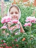 Barn i trädgården med blommor Fotografering för Bildbyråer