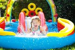 Barn i trädgårds- simbassäng med glidbanan Arkivfoton