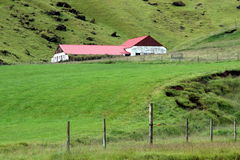 Barn in Iceland. A long low barn is shown against a hillside in rural Iceland Royalty Free Stock Photography