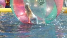 Barn inom stor uppblåsbar boll på vattenyttersida arkivfilmer