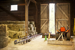 Barn interior with hay bales and farm equipment Stock Photos
