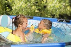 Barn kan simma i den utomhus- pölen arkivbilder