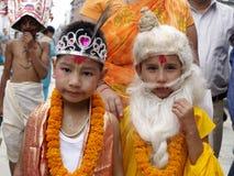Barn klädde som hinduiska gudar i Gai Jatra (festivalen av kor) Arkivfoton