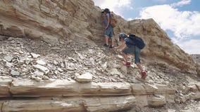 Barn klättrar vagga små handelsresande med ryggsäckar två små flickor på en vandring i bergen lager videofilmer