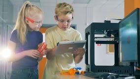 Barn klarar av ett vetenskapligt experiment med hjälpen av en minnestavladator stock video