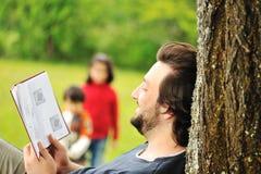 Barn kopplad av faderavläsningsbok royaltyfri bild