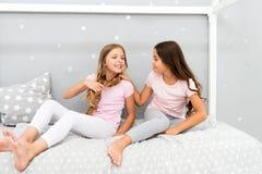 Barn kopplar av och ha gyckel i afton Systerfritid Flickor i gullig pyjamas spenderar tid tillsammans i sovrum systrar arkivfoton