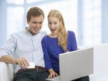 Barn kopplar ihop shopping i internet med kreditkorten Royaltyfria Foton