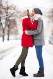 Barn kopplar ihop att kyssa på vinterdag Arkivfoto