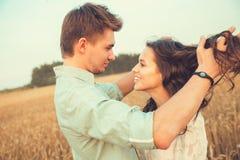 Barn kopplar ihop förälskat utomhus- krama för par Förälskat bli för unga härliga par och kyssa på fältet på solnedgång Arkivbilder