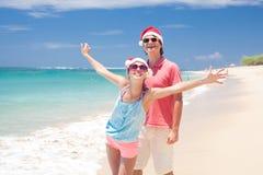 Barn kopplar ihop i santa hattar som skrattar på tropisk strand. nytt år Arkivbilder