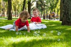 Barn kopplar samman lek på gräset Fotografering för Bildbyråer