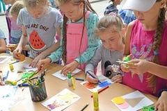 Barn kopplas in i applique Mästarklass för barn` s i den öppna luften arkivfoton