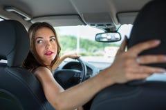 Barn kvinna som kör en bil arkivbilder