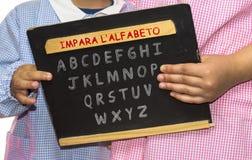 Barn lär alfabetsvart tavla Arkivbilder