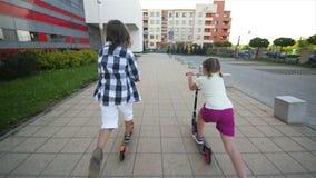 Barn lär att rida sparkcykeln på solig sommardag Ungelek utomhus med sparkcyklar Aktiv fritid och utomhus- sport