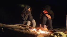 Barn ler ungar, tonårigt som drinkte sitter vid branden på nattlägereld lopp som fotvandrar campa livsstil för affärsföretag arkivfilmer