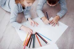 Barn ligger på golvet i pyjamas och drar med blyertspennor Gullig barnmålning vid blyertspennor Royaltyfri Foto