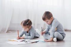 Barn ligger på golvet i pyjamas och drar med blyertspennor Gullig barnmålning vid blyertspennor Royaltyfria Bilder