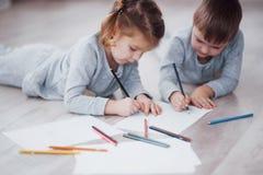 Barn ligger på golvet i pyjamas och drar med blyertspennor Gullig barnmålning vid blyertspennor Arkivfoto