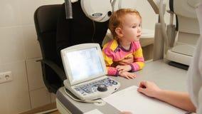 Barn - liten flicka - patient i ögonläkarerum - barn med mamman på på konsultationen Royaltyfria Bilder