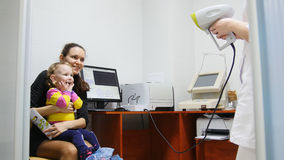 Barn - liten flicka - patient i ögonläkarerum - barn med mamman på på konsultationen Arkivbild