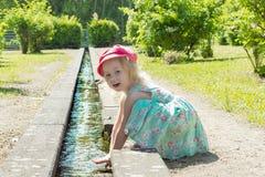 Barn Liten flicka som spelar med vatten i en liten vik på en varm solig dag Arkivbild