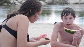 Barn lurar tonåringar på stranden som vilar att skratta och att äta vattenmelonultrarapidvideoen livsstilpojke och flicka arkivfilmer