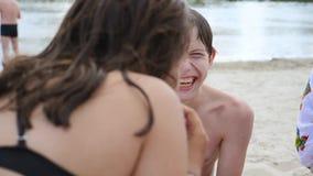 Barn lurar tonåringar på stranden som vilar att skratta och att äta vattenmelonultrarapidvideoen pojke och flicka som vilar på arkivfilmer