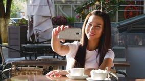 Barn lycklig attraktiv kvinna som dricker kaffe i ett kafé som tar selfies lager videofilmer