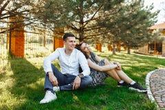 Barn lyckligt och att älska par, tillsammans sitta på gräset i parkera, och tyckande sig om, annonserande och insättande text Royaltyfri Foto