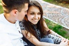 Barn lyckligt och att älska par, tillsammans sitta på gräset i parkera, och tyckande sig om, annonserande och insättande text Royaltyfria Bilder