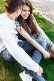 Barn lyckligt och att älska par, tillsammans sitta på gräset i parkera, och tyckande sig om, annonserande och insättande text Arkivfoto