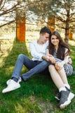 Barn lyckligt och att älska par, tillsammans sitta på gräset i parkera, och tyckande sig om, annonserande och insättande text Fotografering för Bildbyråer