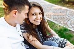 Barn lyckligt och att älska par, tillsammans sitta på gräset i parkera, och tyckande sig om, annonserande och insättande text Royaltyfri Fotografi