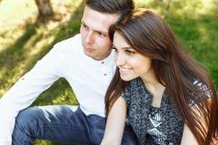 Barn lyckligt och att älska par, tillsammans sitta på gräset i parkera, och tyckande sig om, annonserande och insättande text Arkivbild