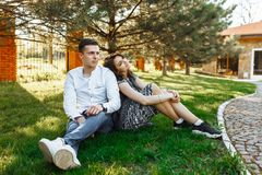 Barn lyckligt och att älska par, tillsammans sitta på gräset i parkera, och tyckande sig om, annonserande och insättande text Royaltyfri Bild