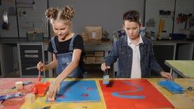 Barn målar med borstar I hantverkseminarium Skola-åldrades barn som arbetar tillsammans att måla och att ha gyckel Pait på arkivfilmer