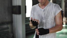 Barn, manlig boxare i boxengidrottshallen som förbereder sig för utbildning eller konkurrens Slår in svart förbinder upp på hans  stock video