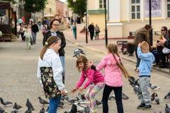Barn matar duvor på en fyrkant i Vitebsk Royaltyfria Foton