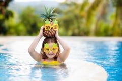 Barn med ananas i simbassäng Ungebad fotografering för bildbyråer