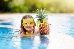 Barn med ananas i simbassäng Ungebad royaltyfri bild