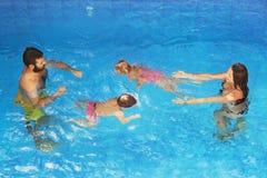 Barn med att simma för föräldrar som är undervattens- i blåttpöl Royaltyfri Bild