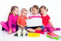 Barn med bärbar dator fotografering för bildbyråer